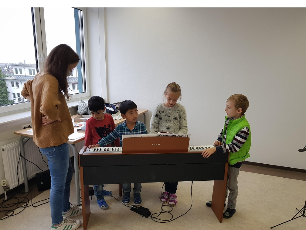 Students of SIS Frankfurt take turns on the piano